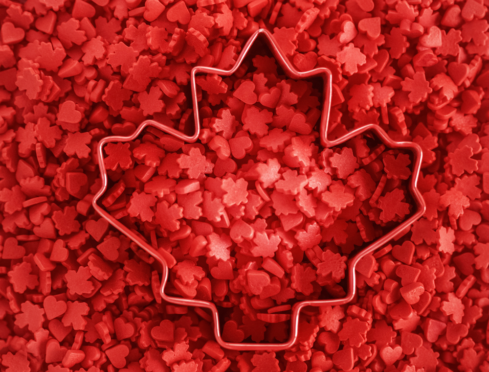 Maple leaf cookie cutter on top of red and heart shaped candies