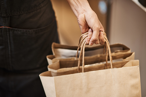 Person carrying brown take out bags