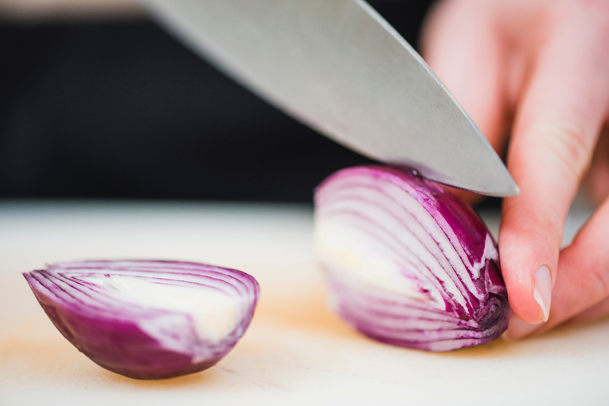 Hands slicing a red onion