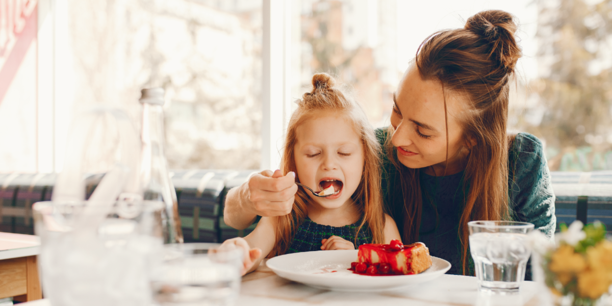 Mother feeding her daughter a piece of cheesecake