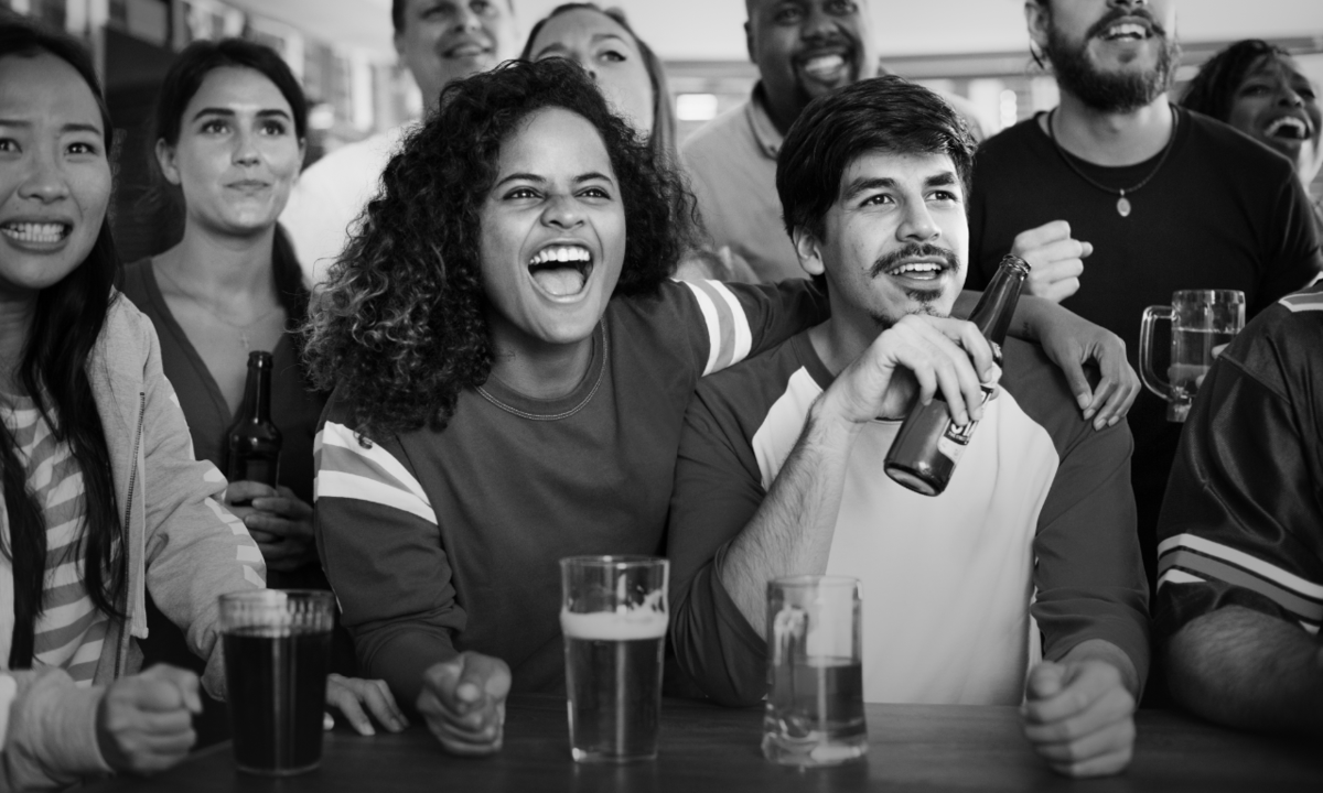 Back and white photo of happy people watching a game