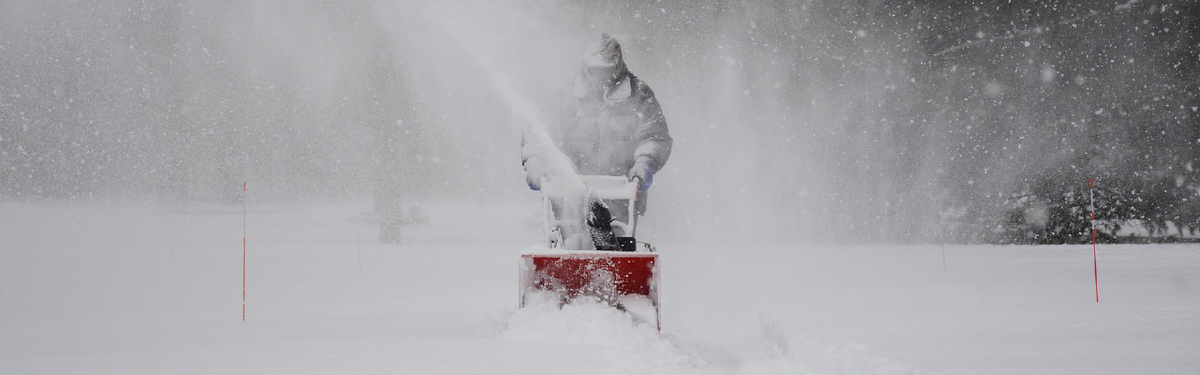 A man using a snowblower in a winter storm