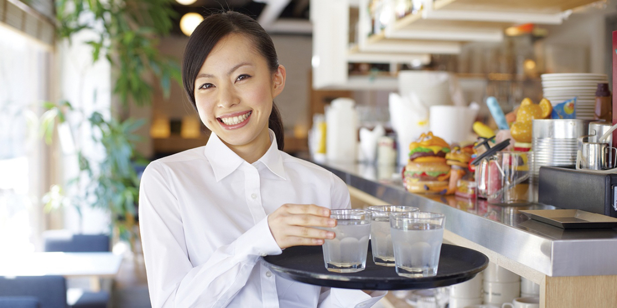 Smiling waitress holding a tray of glasses