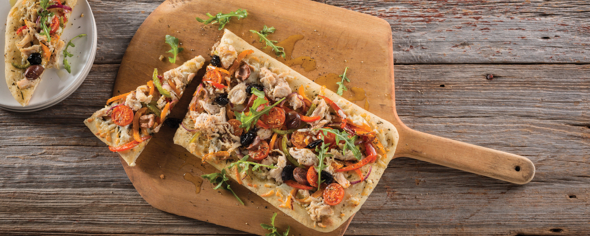 Schneiders pulled chicken with tomotoes olives and other toppings on pizza board