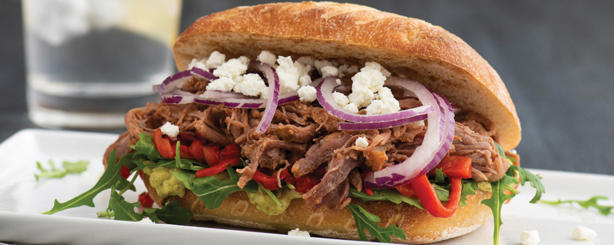 Pulled beef sandwich with onions goat cheese and toppings on a white plate