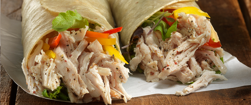 Maple Leaf Piri Piri Pulled chicken wrap with peppers and toppings on wood background