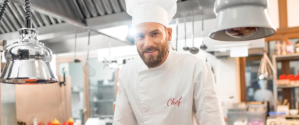 Smiling chef standing in bright kitchen